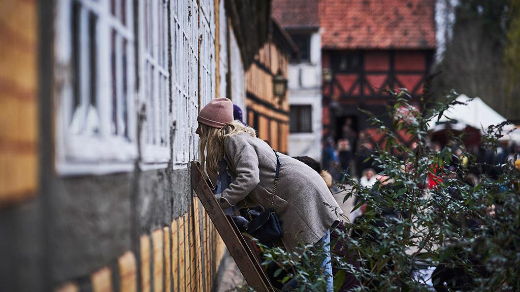 Pige kigger ind af vindue i Den Gamle By